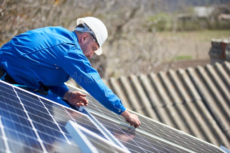Electrician mounting solar panel on roof of modern house. Man engineer in blue suit and protective helmet installing solar photovoltaic panel system stock photography