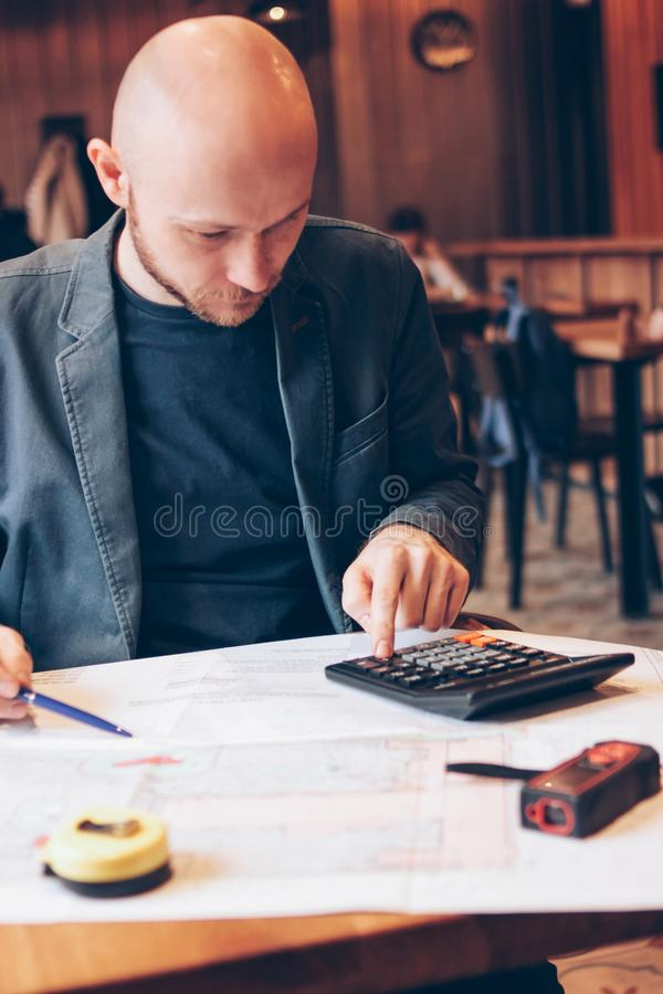 Man engineer designer architect reading drawings at table in cafe stock photo