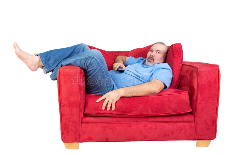 Man engrossed in watching television. Lying barefoot on a red couch with the remote control in his hand and a look of fascinated concentration, isolated on royalty free stock image
