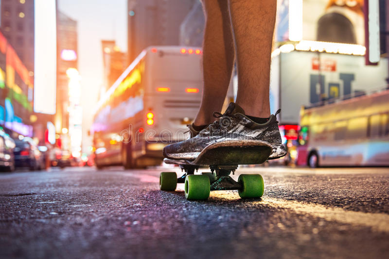 Man enjoy the riding on skateboard on city street at sunset time. Skateboarder people sport concept theme stock photo