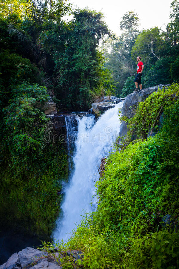Man enjoy scenic views in the morning sun on a background of a tropical waterfall Tegenungan. Man in the morning sun enjoy beautiful views a tropical waterfall royalty free stock images