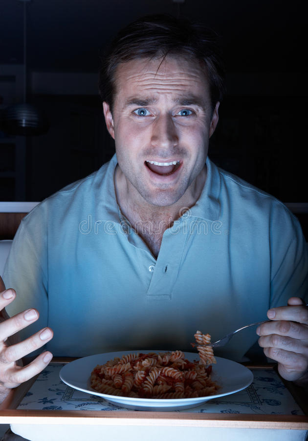 Man Enjoying Meal Whilst Watching TV Royalty Free Stock Photography