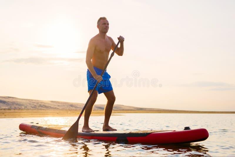Man enjoying ride on paddle board stock photos
