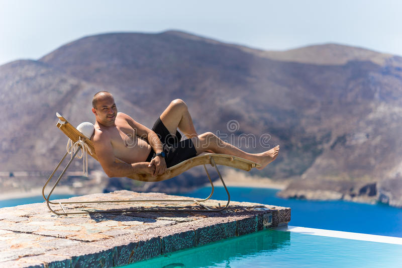 Man Enjoying Summer. Portrait of a man enjoying the sea and summer vacation by the pool on a resting chair stock photos