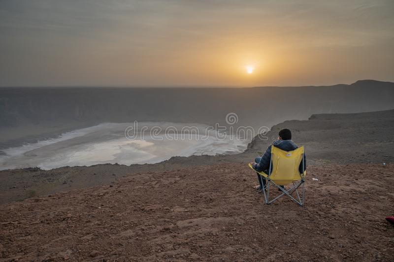 Man in a camping chair at a vulcanic crater during sunrise Al Wahbah crater in Saudi Arabia. A man is enjoying the sunset at a vucanic crater royalty free stock photography