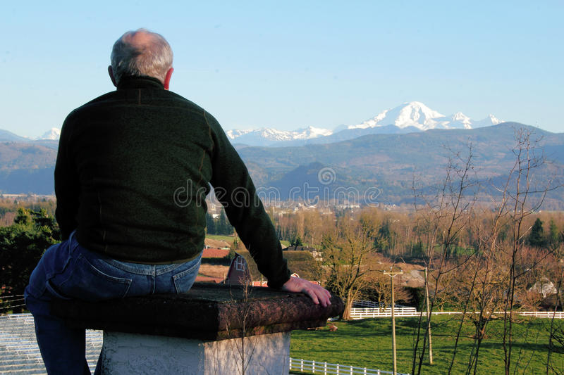Man Enjoys View of Mount Baker. A middle aged man enjoys the view of Washington's Mount Baker stock image