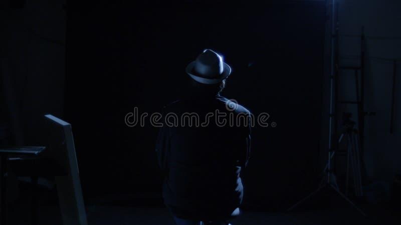 Man ensamt sammanträde på en fåtölj, bakre sikt Mannen i hatten sitter på en stol i mörkret arkivbild