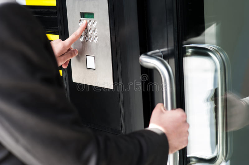 Man entering security code to unlock the door. Businessman entering safe code to unlock the door stock image