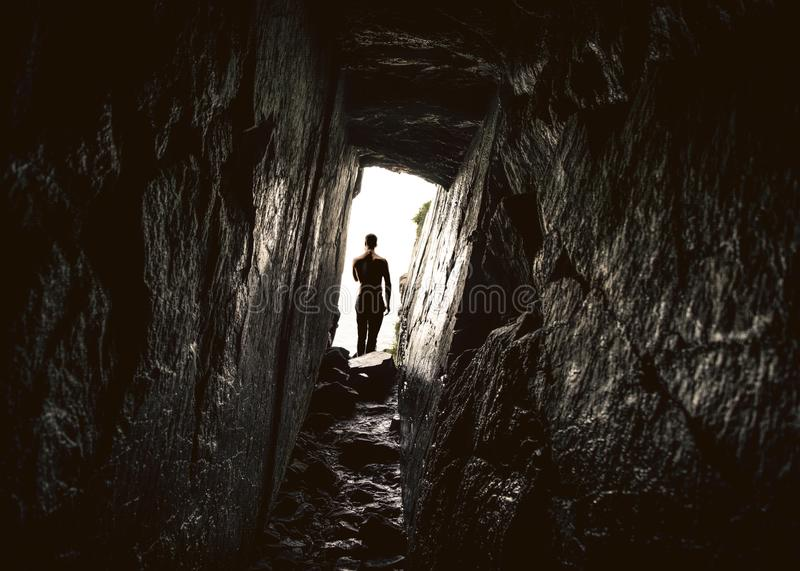 Man in the entrance of a deep narrow cave. Silhouette of a man standing in the light in front of the exit of a deep and narrow rock cave. Photo taken from stock photography