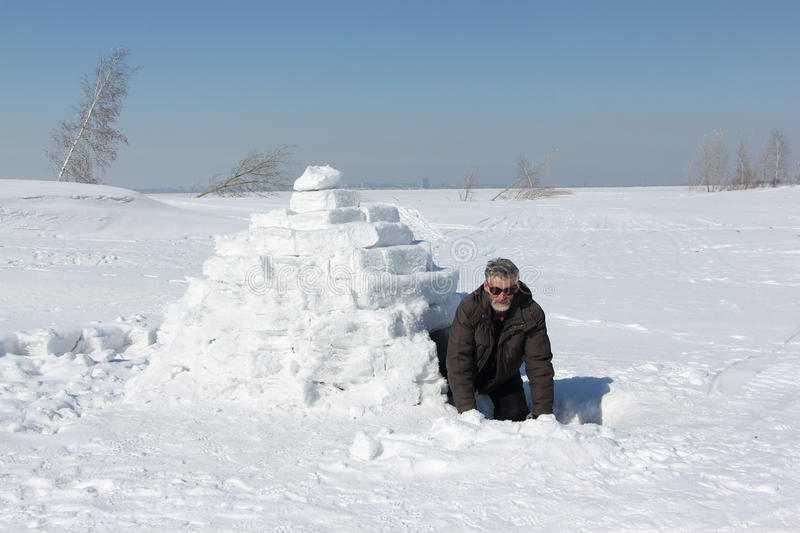 Man at the entrance to an igloo. Man at the entrance to igloo royalty free stock photos