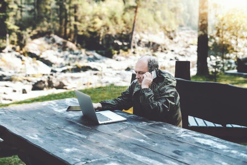 Man entreprenören med bärbara datorn som talar på telefonen i skog arkivfoto