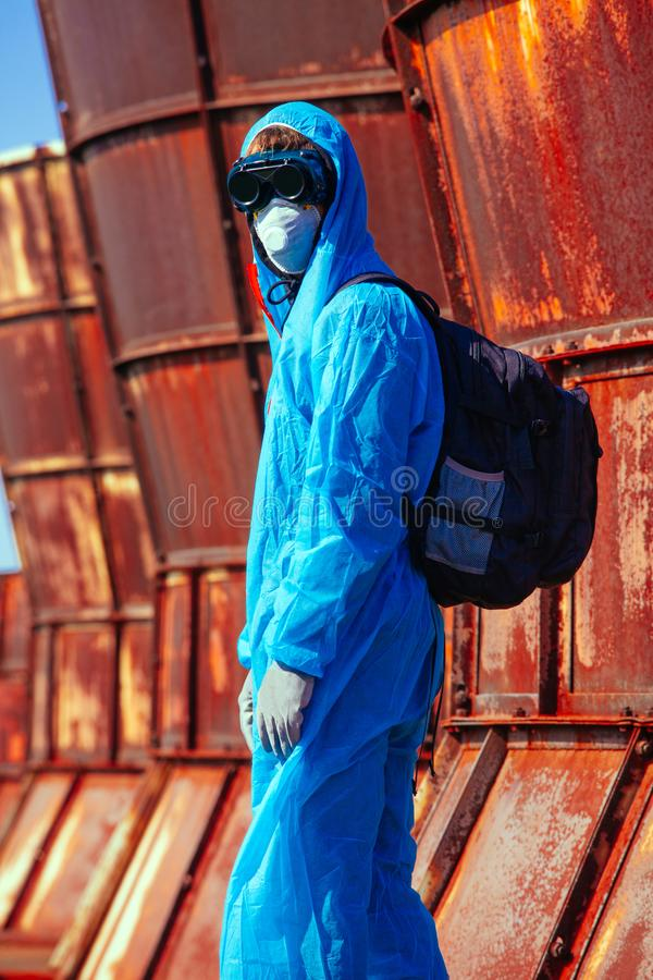 Man environmental mask fire pack disguise facemask bitmask protective overall blue orange rast plant factory disused catastrophe. Men in blue protective overall royalty free stock photography
