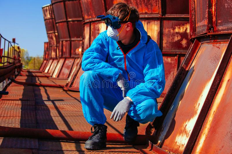 Man environmental mask fire pack disguise facemask bitmask protective overall blue orange rast plant factory disused catastrophe. Men in blue protective overall stock photos