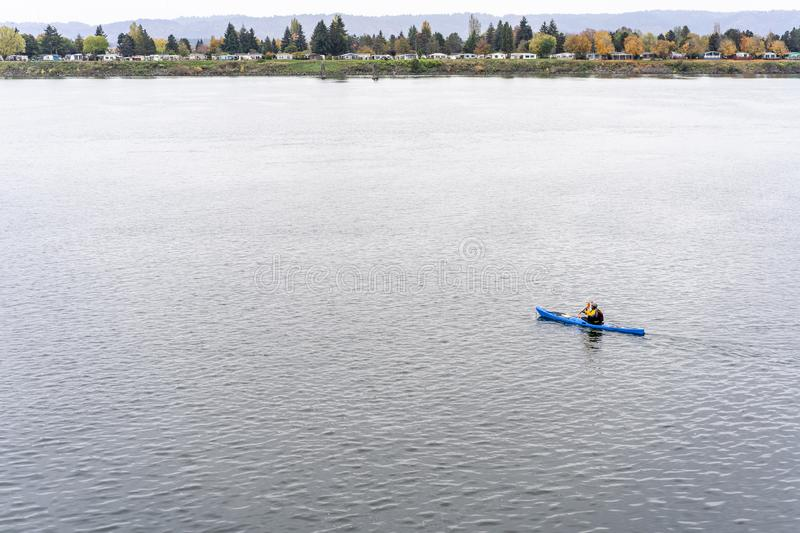 Man in equipment rides kayak on the Columbia River with number of houses on the shore. An enthusiast Man in sportive equipment and life vest for safety love royalty free stock images