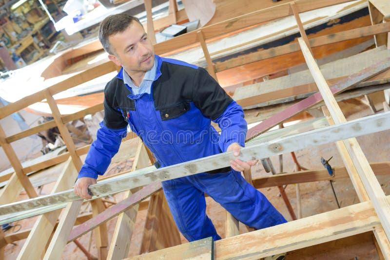 Man erecting timber frame. Man stock photos