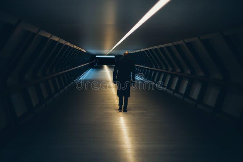 Man on Escalator in Illuminated Room royalty free stock photo