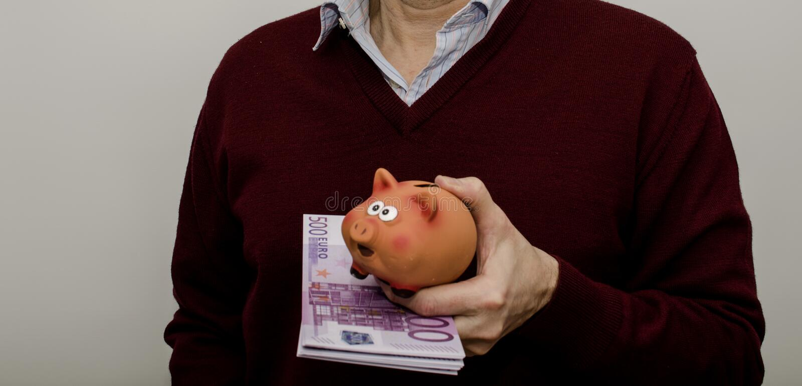 Man with 500 euro bills and piggy bank in hand royalty free stock photography