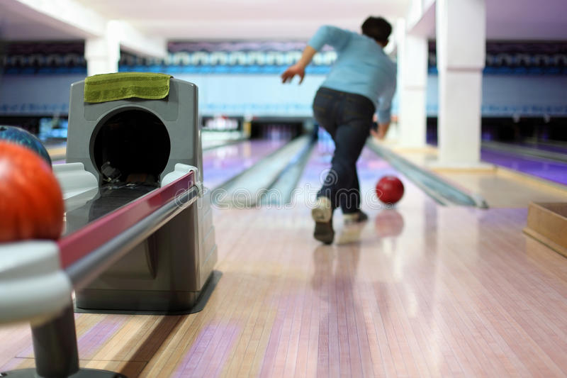 Man exactly throws up ball on skittles. In bowling club royalty free stock photos