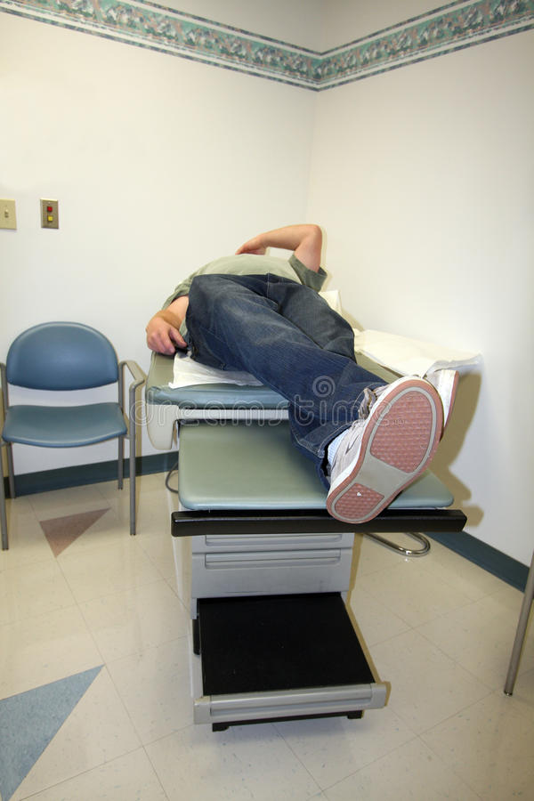 Man on exam table in doctor's office stock photography