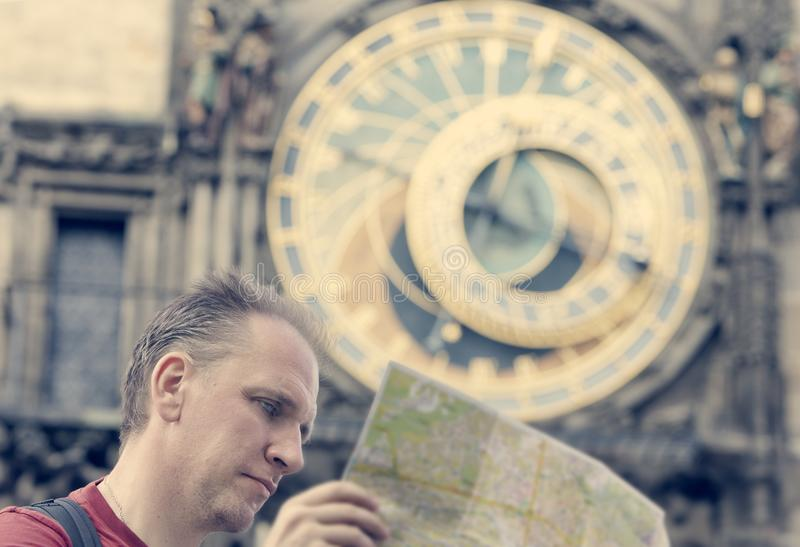 Man examines the map on background of historical medieval astronomical Clock on the Old Town Hall in Prague, Czech Republic, retro stock images