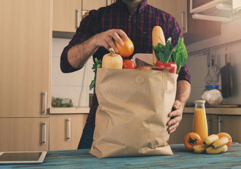 Man examines a paper bag with different healthy food. On a wooden table in the home kitchen royalty free stock image