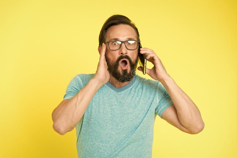 Man excited about mobile phone opportunities. Hipster cheerful use smartphone. Man happy user of modern smartphone. Stay stock image