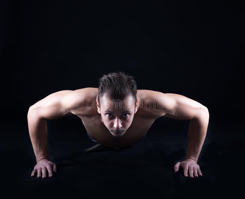 Man execising push ups. Concentrated man training and exercising push ups at studio royalty free stock photography