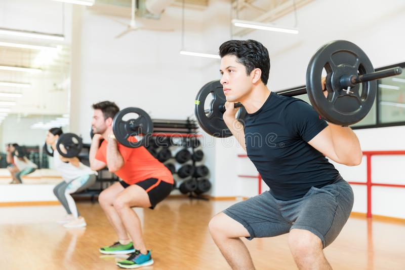 Man Exercising With Barbell In Health Club. Handsome young men exercising with barbell in health club stock image