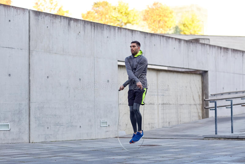 Man exercising with jump-rope outdoors stock image