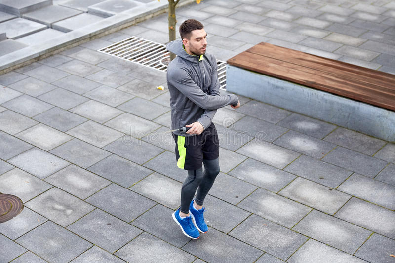 Man exercising with jump-rope outdoors. Fitness, sport, people, exercising and lifestyle concept - man skipping with jump rope outdoors royalty free stock photo