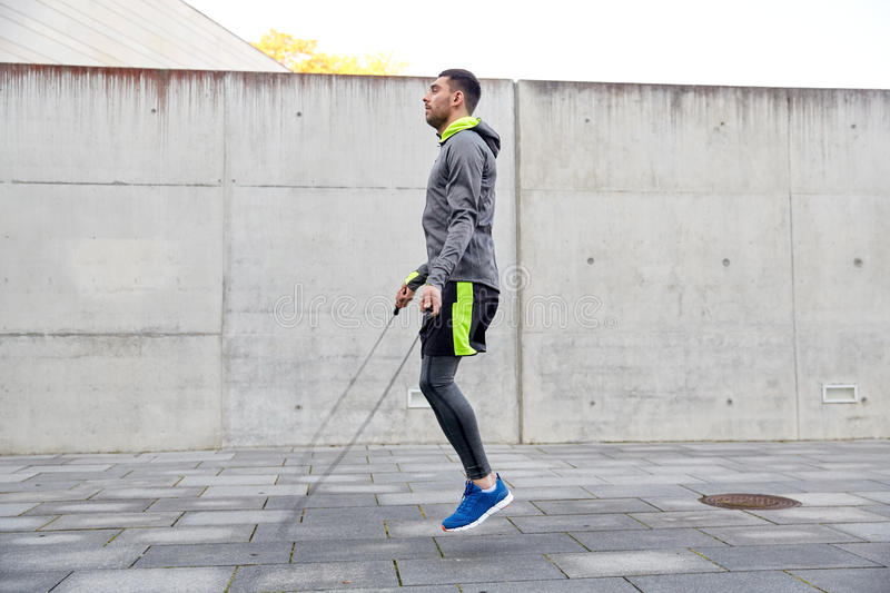 Man exercising with jump-rope outdoors. Fitness, sport, people, exercising and lifestyle concept - man skipping with jump rope outdoors stock photography