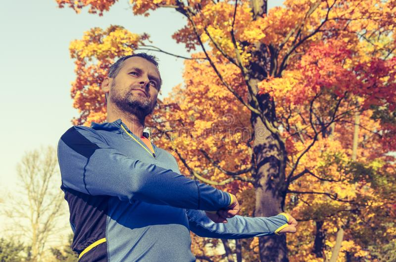 Man exercising in the park in autumn royalty free stock photography