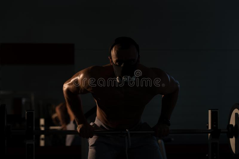 Man Exercising Push-Ups On Barbell In Elevation Mask. Bodybuilder Doing Push Ups On Barbell As Part Of Bodybuilding Training In Elevation Mask stock photos