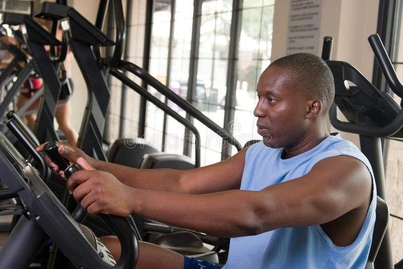 Man Exercising On Stationary Cycle Royalty Free Stock Photography