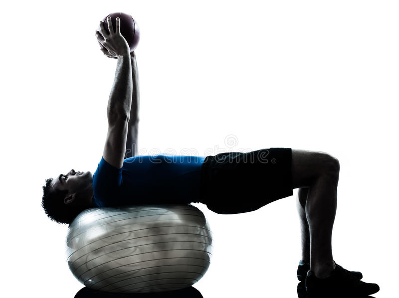 Man exercising workout fitness ball posture. One caucasian man exercising workout fitness ball in silhouette studio isolated on white background royalty free stock photography