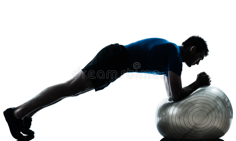 Man exercising workout fitness ball posture. One caucasian man exercising workout fitness ball in silhouette studio isolated on white background royalty free stock images