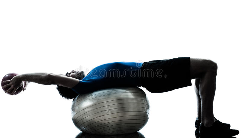 Man exercising workout fitness ball posture. One caucasian man exercising workout fitness ball in silhouette studio isolated on white background royalty free stock photos