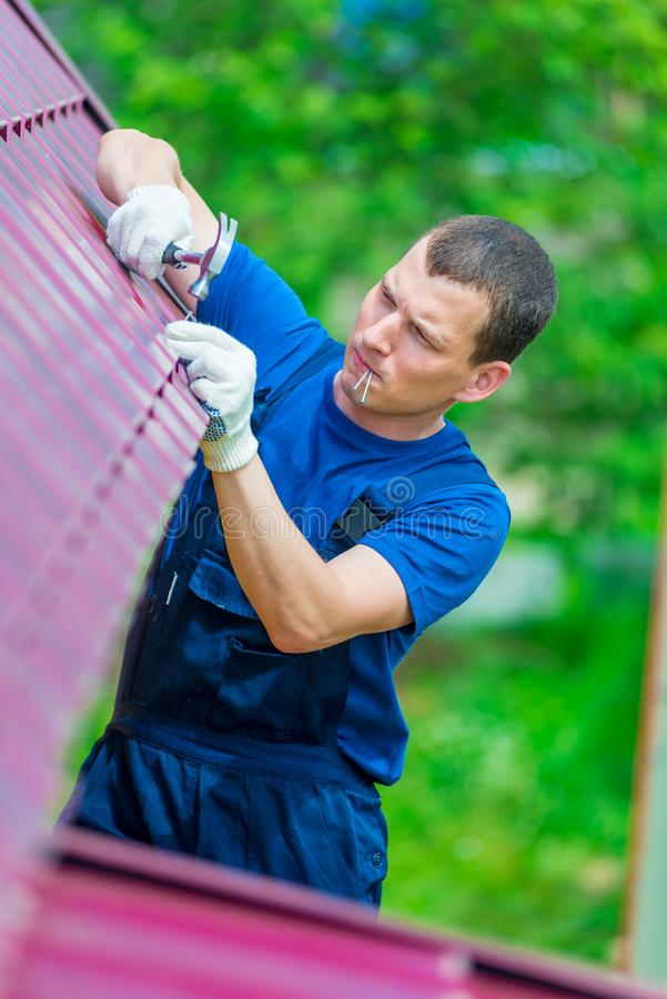 The man is an experienced worker repairing the roof of a residential private house royalty free stock images
