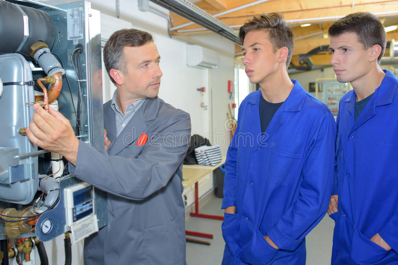 Man explaining workings boiler to two trainees stock image