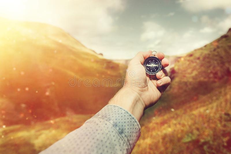 Man Explorer Searching Direction With Compass In Summer Mountains, Hand Point Of View Shot royalty free stock image