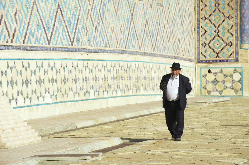 Man explores mausoleum of Khoja Ahmed Yasavi in Turkistan, Kazakhstan. TURKISTAN, KAZAKHSTAN - SEPTEMBER 20, 2011: Unidentified man walk around the medieval stock image
