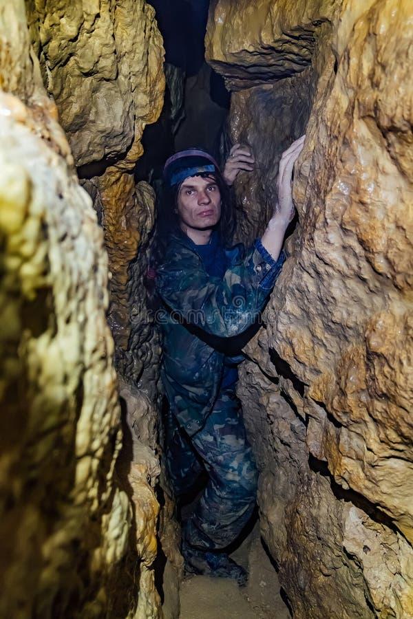 Man explores narrow cave royalty free stock photography