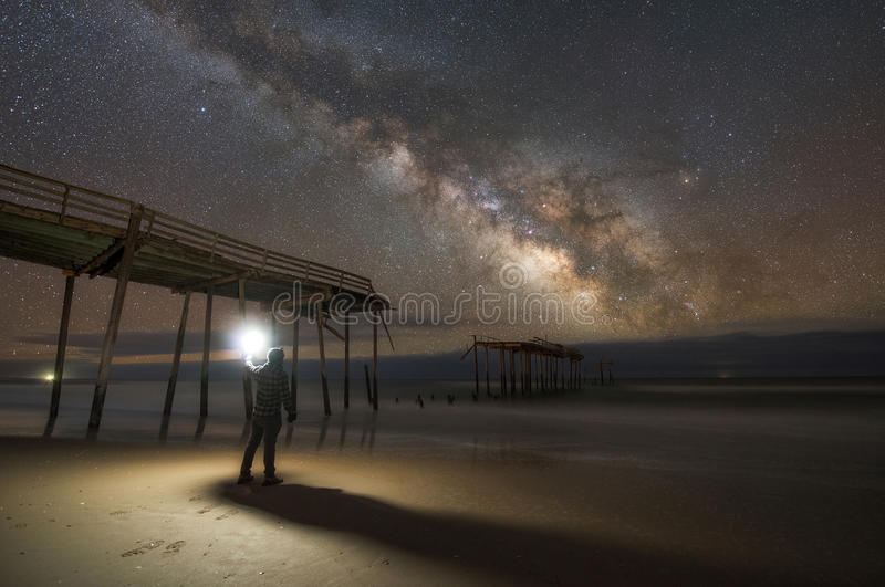 Man exploring a damaged pier at night. The damaged Frisco Pier in North Carolina still stands under the night sky royalty free stock photo