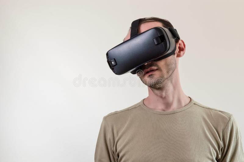 Man exploring modern technology virtual reality with head mounted display on white background stock photography