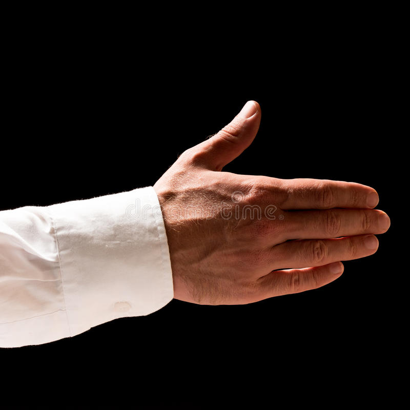 Man extending his hand in a handshake. Man in shirt sleeves extending his hand in a handshake in greeting, to finalise a deal, in partnership, help or royalty free stock image