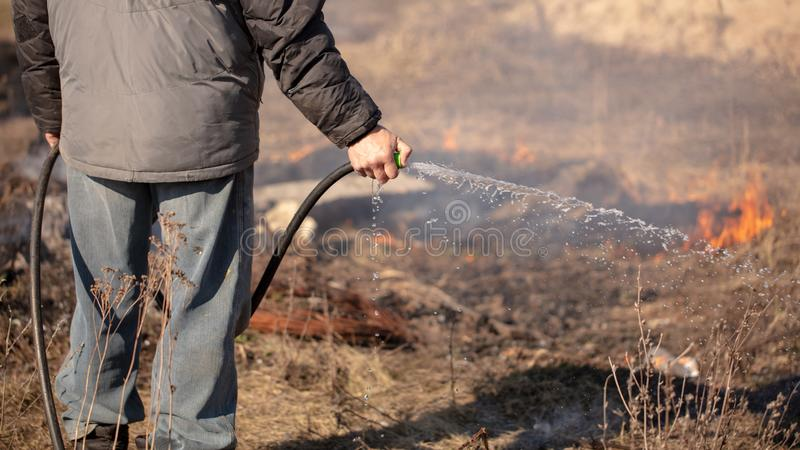 A man extinguishes the burning grass with water stock image