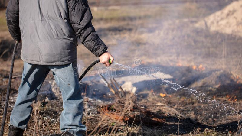 A man extinguishes the burning grass with water stock photography