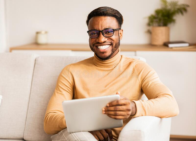 Man In Eyeglasses Holding Tablet Sitting On Couch At Home stock photo