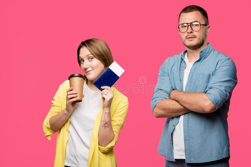 man in eyeglasses standing with crossed arms and looking at camera while smiling woman holding passport, boarding pass and coffee  royalty free stock photo