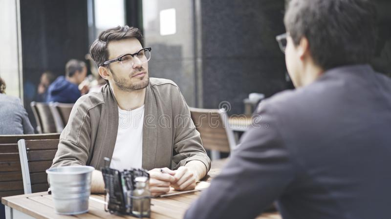 A man in eyeglasses talking listening to his friend at cafe outdoors stock image